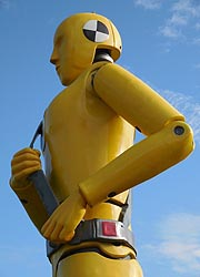 [photo, Oversized replica of yellow crash-test dummy with safety belt, Motor Vehicle Administration, 6601 Ritchie Highway, NE, Glen Burnie, Maryland]
